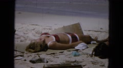 1965: woman sunbathing in a bikini and children jumping and playing in the ocean Stock Footage