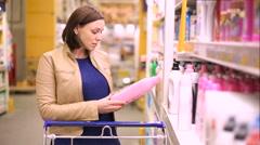 Woman buys shampoo Stock Footage