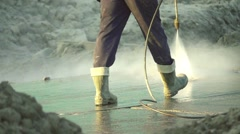 Slow motion builder washing the road with a high-pressure washers Stock Footage