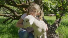 Medium slow motion shot of girl petting lamb in field / Springville, Utah, Stock Footage