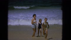1965: a mother and two girls are walking back to shore from the edge  Stock Footage