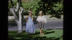 1965: two girls playing pretend in green grassy yard above street HAWAII Stock Footage