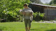 Medium slow motion shot of boy carrying and petting lamb / Springville, Utah, Stock Footage
