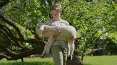 Medium shot of boy holding and petting lamb / Springville, Utah, United States Stock Footage