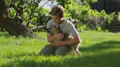 Medium panning shot of kneeling boy playing with dog in field / Springville, Stock Footage