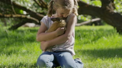 Medium panning shot of kneeling girl hugging rabbit in field / Springville, Stock Footage