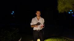 European Conjurer Shuffles Cards against Dark Park Stock Footage