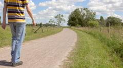 Man walking on rural road in beautiful scenic landscape, Sweden Stock Footage