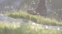 DOF: Detail of leather mountain shoes and woman stepping on meadow and bedrock Stock Footage