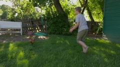 Medium slow motion tracking shot of boy chasing chicken / Springville, Utah, Stock Footage