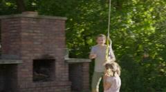 Wide tracking shot of boy pushing girl on rope swing / Springville, Utah, United Stock Footage