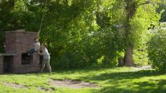 Wide slow motion panning shot of boy pushing girl on rope swing / Springville, Stock Footage