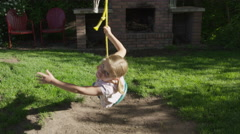 Medium slow motion shot of girl looking at camera on rope swing / Springville, Stock Footage