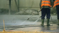 Slow motion construction workers wash the road with high-pressure washers Stock Footage