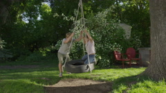 Wide slow motion shot of boy and girl on tire swing / Springville, Utah, United Stock Footage