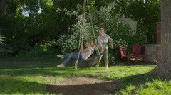 Wide slow motion panning shot of boy pushing girl on tire swing / Springville, Stock Footage