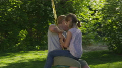 Medium slow motion tracking shot of girl on lap of boy on rope swing / Stock Footage