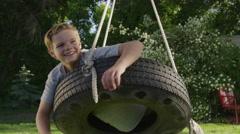 Medium panning shot of boy smiling on tire swing / Springville, Utah, United Stock Footage