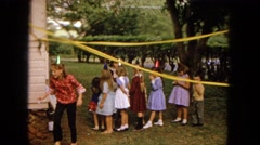 1965: girl in red top and green hat walks away for other children at a birthday Stock Footage