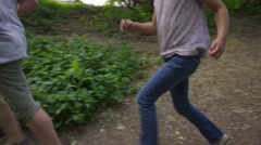 Wide slow motion panning shot of boy and girl running through woods / Stock Footage