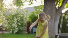 Medium slow motion panning shot of girl dancing in yard / Springville, Utah, Stock Footage