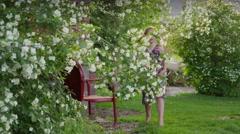 Medium panning shot of girl skipping in yard picking flower petals / Stock Footage