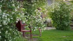 Medium slow motion panning shot of girl skipping in yard picking flower petals / Stock Footage