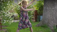 Medium slow motion shot of girl dancing in yard / Springville, Utah, United Stock Footage