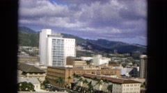 1965: skyscrapers and a small city nestled beside towering mountains  Stock Footage
