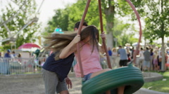 Medium shot of man spinning woman on tire swing at amusement park / Pleasant Stock Footage