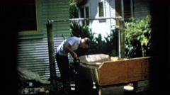 1965: man is repairing a piece of furniture in the backyard while standing Stock Footage