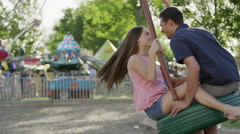 Medium tracking shot of couple spinning on tire swing / Pleasant Grove, Utah, Stock Footage