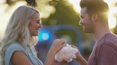 Close up panning shot of couple eating cotton candy and kissing / Pleasant Stock Footage