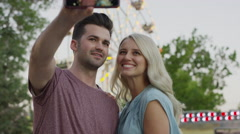 Close up of couple taking cell phone selfie at amusement park / Pleasant Grove, Stock Footage