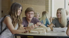 Medium shot of students examining cell phone in school cafeteria / Mapleton, Stock Footage