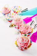 Pink birthday cupcakes  with whipped cream and cookware Stock Photos