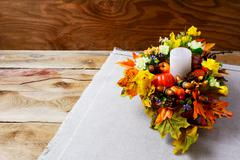 Thanksgiving  centerpiece with candle and artificial fall leaves Stock Photos