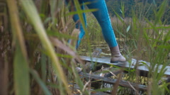 CU on woman legs walking on a damaged abandoned wooden pier Stock Footage