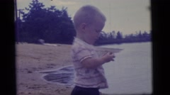 1965: a young male toddler finds a small rock on the bank of a river  Stock Footage