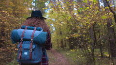 TRACKING FOLLOW Active Caucasian female with a backpack hiking in autumn forest Stock Footage