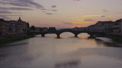 Wide shot of silhouette of bridge over urban river / Florence, Tuscany, Italy Stock Footage