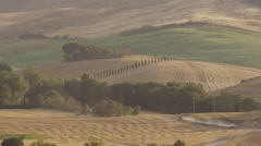 Wide shot of car driving on dusty rural road / Pienza, Tuscany, Italy Stock Footage