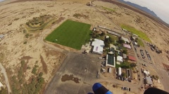 Skydiver parachuting in sky above sands of Arizona. Landing on green field Stock Footage