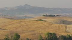 Wide panning shot of hay bales on rolling landscape / Pienza, Tuscany, Italy Stock Footage