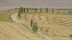 Wide shot of women running on winding rural road / Pienza, Tuscany, Italy Stock Footage