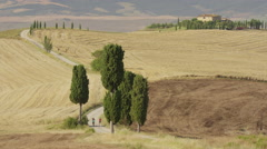 Wide high angle shot of women running on winding rural road / Pienza, Tuscany, Stock Footage
