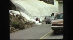 1967: people walking and driving along a rugged ice-covered mountain  Stock Footage