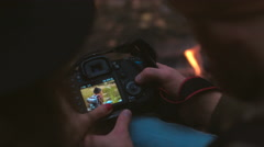 Hikers checking the pictures on a modern DSLR camera near bonfire Stock Footage