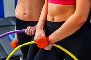 Bare female belly with dumbbells and hoop at gym. Stock Photos