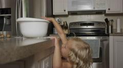 Medium shot of girl taking cookie dough from bowl in kitchen / Orem, Utah, Stock Footage